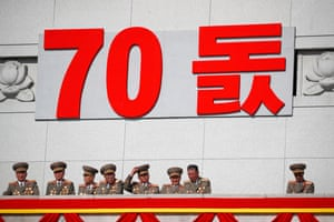 Military officers sit under a sign marking the 70th anniversary