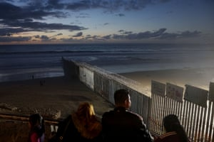 People at the US-Mexico border fence at Las Playa in Tijuana, Mexico.