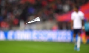 A paper airplane is thrown onto the field.