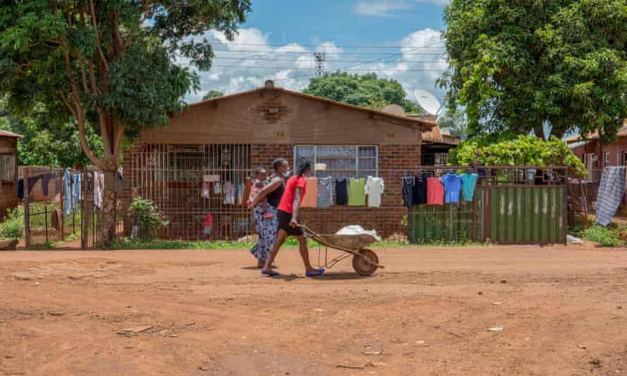 Women walk in the streets of Kuwadzana.