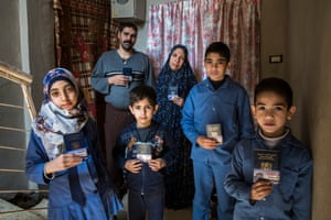 Zakwan Mamdouh Mo'en, Um Mamdouh and their four children hold up their remaining possessions: their Syrian passports