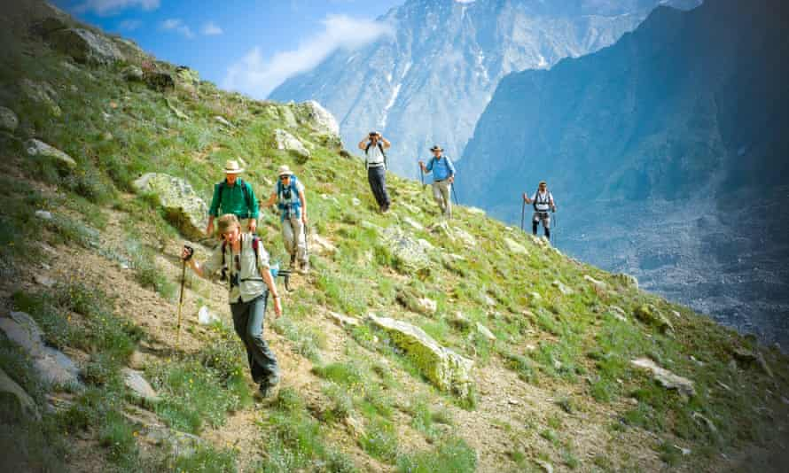 A line of trekkers on a hillside, jagged mountain peaks behind