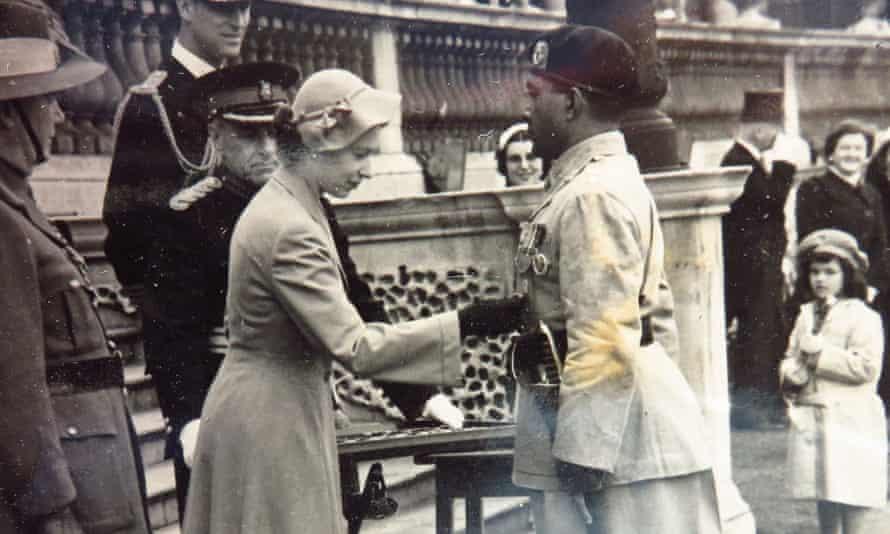Maj Gen Anton Muttukumaru receives the Coronation medal from the Queen