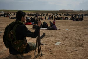 A member of SDF watches evacuees from Baghouz
