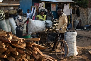 A man buys charcoal from a vendor in the market in Gulu.