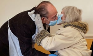 Bob Underhill, 84, and his wife Patricia, 82, kiss through face masks as they are allowed to visit with physical contact for the first time since March