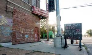 An abandoned building is adorned with chalk graffiti pleading for an end to violence in north St Louis.