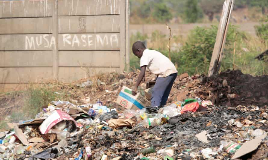 A child scavenges for plastic waste and cardboard for resale in the Harare township of Warren Park. Zimbabwe's economic crisis means there is no treatment for most drug addicts.