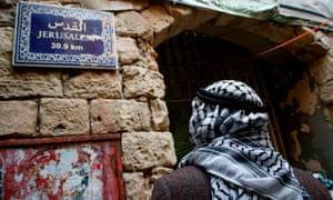 An elderly Palestinian man walks past a street sign indicating the distance to Jerusalem in Hebron in the Israeli-occupied West Bank on Friday.