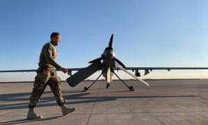 US forces walking past a drone in the Ain al-Asad airbase in the western Iraqi.