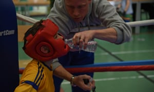 A young boy in a boxing ring.
