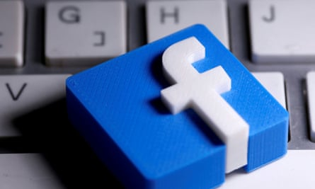 A 3D-printed Facebook logo is seen placed on a keyboard