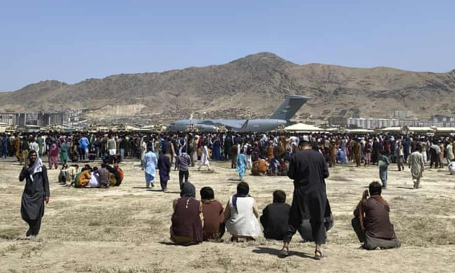 Hundreds of people gather near a U.S. Air Force C-17 transport plane at the perimeter of the international airport in Kabul, Afghanistan. A school district in a San Diego suburb that is home to a large refugee population says many of its families who had taken summer trips to Afghanistan to see their relatives have gotten stuck there with the chaos following the withdrawal of U.S. troops. (AP Photo/Shekib Rahmani)