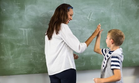 Happy teacher and school boy giving high five in classroom