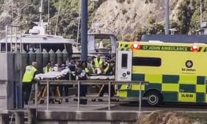 In this image made from video, injured from White Island volcanic eruption are ferried into waiting ambulances in Whakatane, New Zealand.