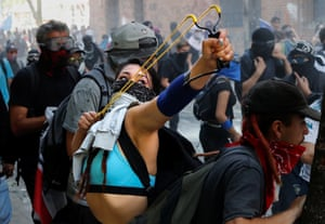 Santiago, Chile A young woman uses a catapult during Protests against Chile's government in Santiago.