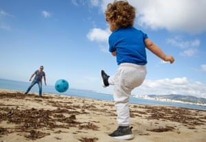 A child plays football with his father at Can Pere Antoni Beach in Palma de Mallorca