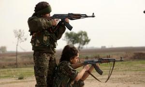Two women in the newly formed Syriac Christian female militia fire their Kalashnikovs at a training camp.