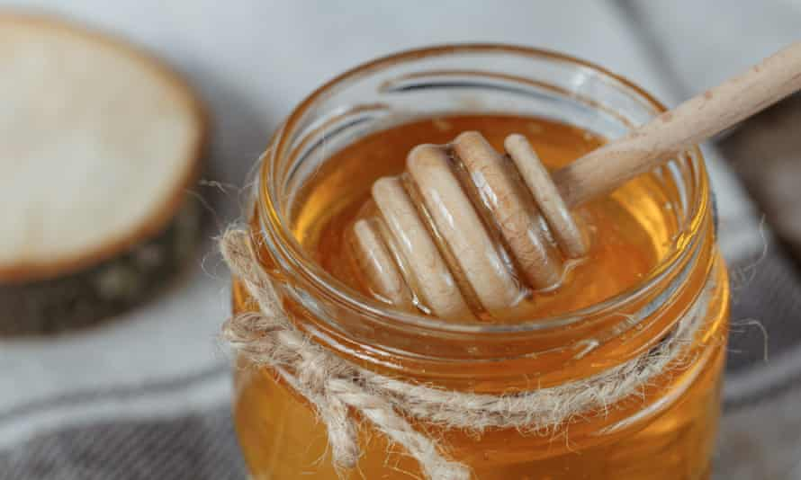Glass pot of honey on a rustic background.