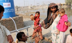 People collect clean drinking water from a tapstand in the town of Ghari Kharo, in the western Sindh Province of Pakistan.
