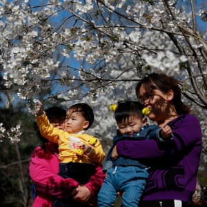 Women and their children look at cherry blossoms in Yuyuantan Park in Beijing, China, 27 March