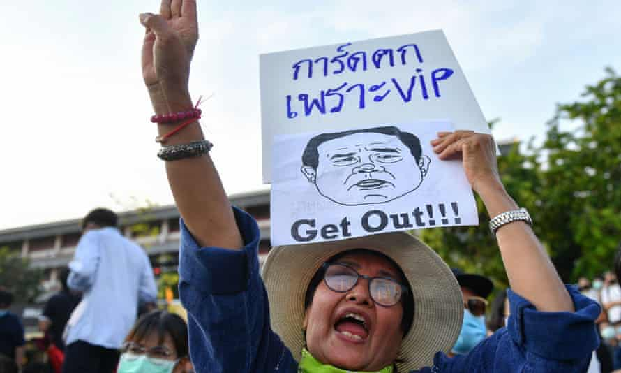 A protester holds a sign depicting the Thai prime minister, Prayut Chan-o-cha.