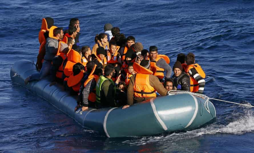 Refugees in inflatable dinghy being towed