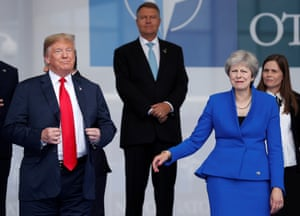 Donald Trump gathers his poise as he waits for the official photographs with Theresa May and other leaders