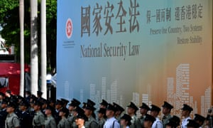 """""""Attendees from various forces stand next to a banner supporting the new national security law during a flag-raising ceremony to mark China's National Day celebrations early morning in Hong Kong on July 1, 2020. - Hong Kong marks the 23rd anniversary of its handover to China on July 1 under the glare of a new national security law imposed by Beijing."""""""