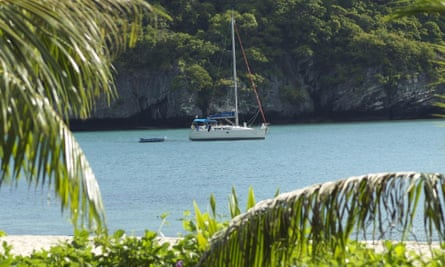 A yacht on the water framed by palm trees Sunsail Thailand