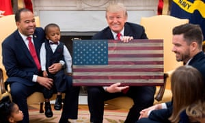 Donald Trump holds an American flag made of wood as he speaks about tax reform alongside 'ordinary Americans' in the Oval Office this month.