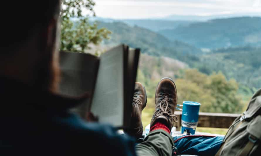 man in hiking boots reading book overlooking hilly view