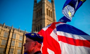 An anti-Brexit protester wearing a European Union flag cap, flies European and Union flags outside the Houses of Parliament in London