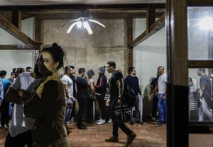 Partygoers at a hall in Sao Paulo, Brazil, wait to have their ID cards photographed by police after the force broke up their social gathering in an operation against illegal and clandestine gatherings.