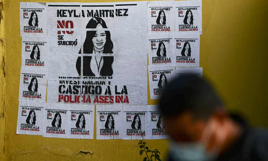 A member of the Honduran national police stands in front of a signal that reads 'Keyla Martinez didn't kill herself, investigate and punish the police', in La Esperanza, Honduras.