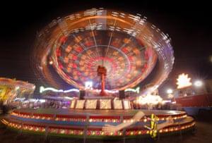 A child runs past a merry-go-round in Roşiorii de Vede