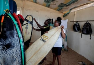 """Khadjou checks a surf board as she talks to her coach Rhonda Harper, the founder of Black Girls Surf (BGS). Sambe went to California in 2018 to train with BGS. Harper said she arrived without a cent in her pocket, speaking no English and with a wild, free surf style that needed taming to fit the structure of surf competitions. """"It's like trying to take a tornado right, and put a rope around it, wrangle that thing down. Because she is such a dynamic surfer that it's hard."""" Harper said BGS started looking for female surfers in Africa because of the lack of representation in professional surfing"""
