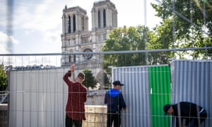 Workers installing protection panels to secure a boundary around Notre Dame Cathedral ahead of the 10-day decontamination operation.