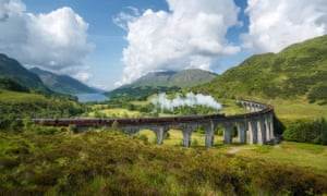 Vintage steam train passes the famous Glenfinnan viaduct with views over Loch Shiel