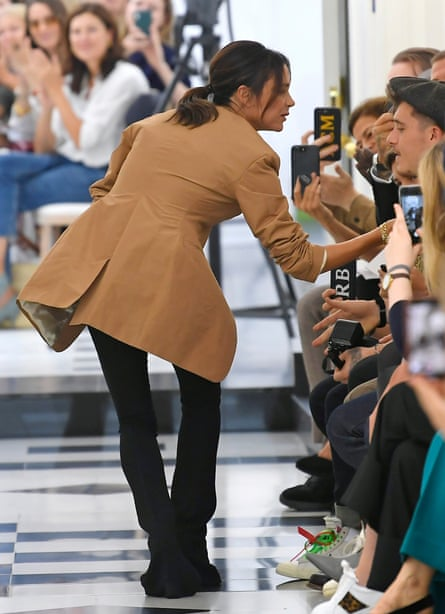 Victoria Beckham on the catwalk at London fashion week in September 2018, talking to son Brooklyn (in cap)