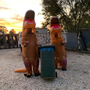 Kim Ross and partner dressed as dinosaurs to wheel out the bins