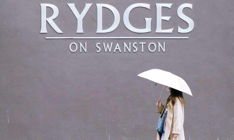 a woman with an umbrella walks by Rydges hotel in melbourne