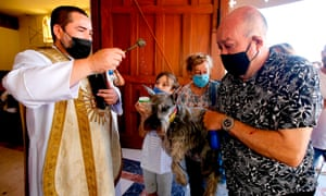 Catholic faithful wearing face masks bring their pets to be blessed at the Church of Saint Francis of Assisi, patron saint of animals, whose feast marks World Animal Day in Zapopan, Jalisco, Mexico on 4 October 2020, amid the Covid-19 coronavirus pandemic.