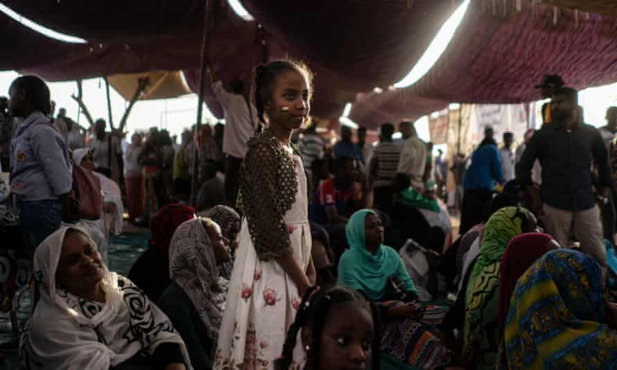 A Sudanese girl watches as protesters demand change following the ousting of Omar al-Bashir