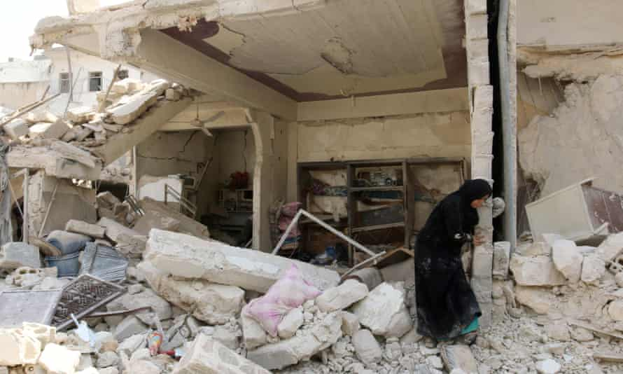 A woman inspects the damage after an airstrike in the Bab al-Nairab neighborhood of Aleppo, Syria, August 2016.