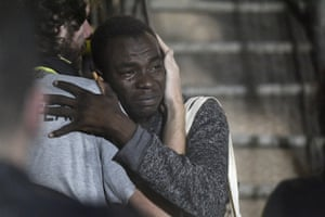 A man cries as he hugs a crew member after disembarking from the Open Arms rescue ship on the Sicilian island of Lampedusa.