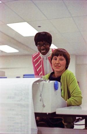 Rosie and Francine, senior computer operators, pose behind a printer