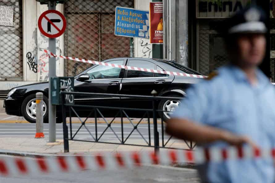 A police officer secures the area around Papademos' car in Athens.