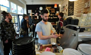 A man makes coffee at a boutique cafe in Brixton.