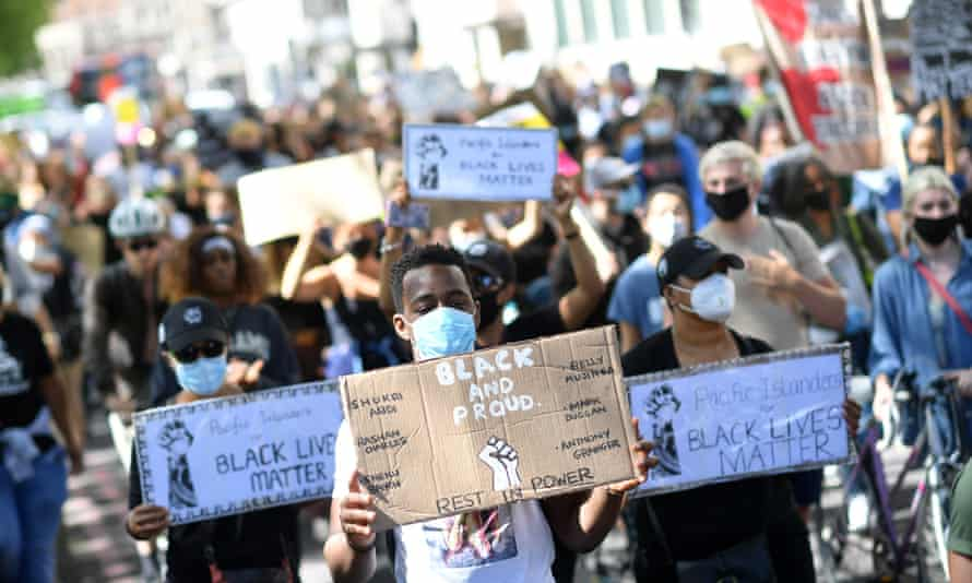 Protesters wearing protective face coverings hold placards as they march down Park Lane in support of the Black Lives Matter movement in London on 5 July